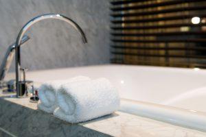 White bathroom towel on a white marble bathtub