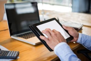 Business executive using digital tablet at desk in office