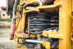 hydraulic flexible pressure pipes and tubes. Close-up of industrial bulldozer with oil leaks