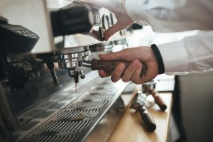 Man hands working with coffee machine at cafe. Close up barista hands preparing making coffee in coffee shop