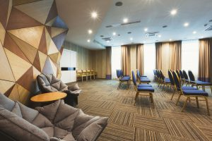 Modern lobby with abstract wooden mosaic wall and armchairs. Rest zone in hotel reception, copy space