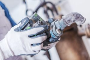 Plumbing Service Work. Plumber with Some Hydraulic System Part in Hand. Closeup Photo